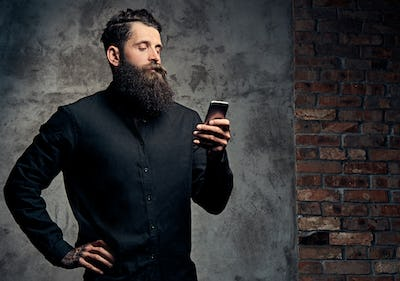 Handsome bearded hipster dressed in a black shirt, using a smartphone, standing in a studio