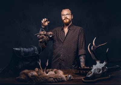 Redhead taxidermist male standing near a table with handmade trophy, owl scarecrow, and the fox skin