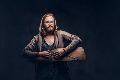 Redhead hipster male playing on a Russian traditional musical instrument - gusli