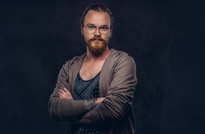 Portrait of a redhead hipster male in a studio. Isolated on the dark background.