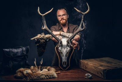 Taxidermist standing near a table with handmade trophy, owl scarecrow, and the fox skin