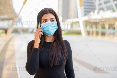 Young Indian woman with mask talking on the phone at the skywalk bridge
