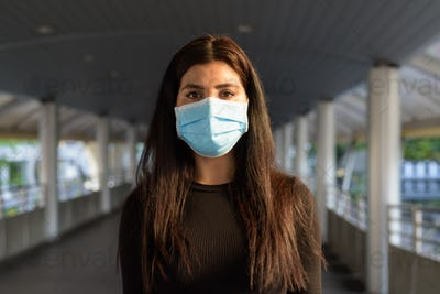 Young Indian woman wearing mask for protection from corona virus outbreak at the footbridge