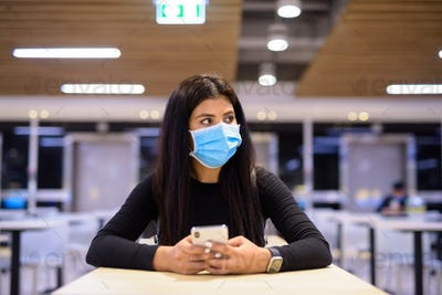 Young Indian woman with mask thinking while using phone and sitting with distance at food court