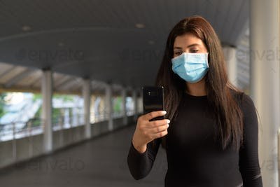 Young Indian woman with mask using phone at the footbridge