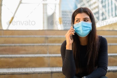 Young Indian woman with mask talking on the phone and sitting by the stairs in city