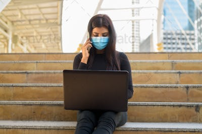 Young Indian woman with mask using laptop and talking on the phone in the city