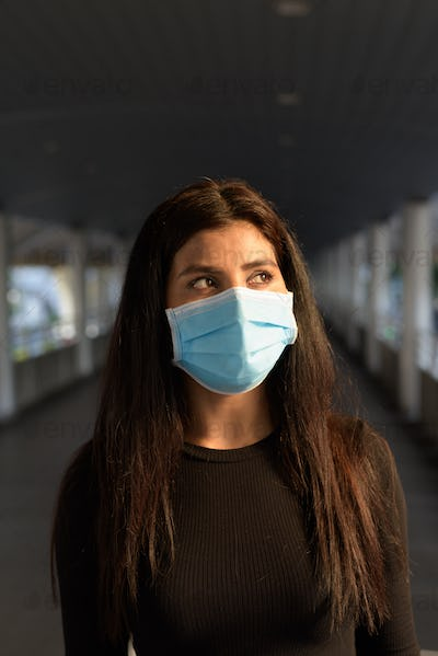 Young Indian woman thinking with mask for protection from corona virus outbreak at the footbridge