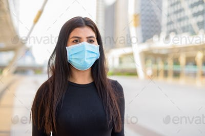 Young Indian woman with mask for protection from corona virus outbreak at the skywalk bridge