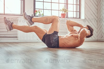 Handsome shirtless muscular male doing abdominal exercises on floor at home.