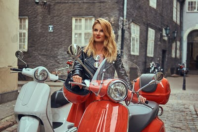 Sexy blonde girl wearing stylish clothes standing on an old narrow street with two retro scooters.