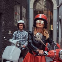 Handsome man and a sexy stylish girl are walking with retro Italian scooters