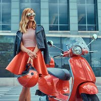 Stylish blonde girl standing near classic Italian scooter against a skyscraper.