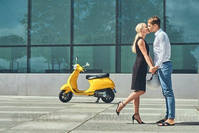 Attractive couple in love - near a yellow classic Italian scooter against a skyscraper.