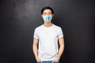 Portrait of young asian guy in glasses standing in white casual shirt over black background
