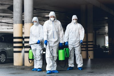 Virologists wearing hazmat suits disinfecting parking with spray chemicals