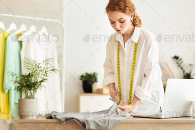 Focused tailor cutting fabric with scissors, sewing costume