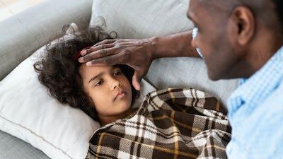 Virus outbreak. Senior African American man touching his granddaughter's forehead, checking