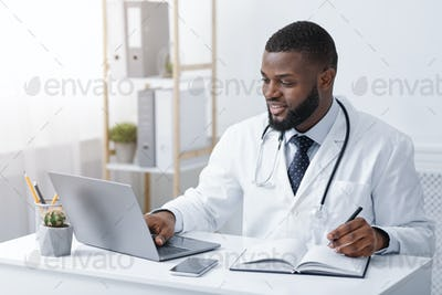 Friendly black doctor making online check up, using laptop
