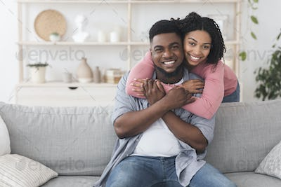Happy african american couple embracing at home and smiling to camera