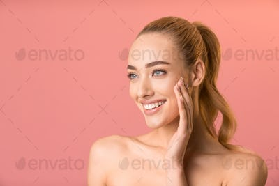 Girl Touching Face Applying Cream Looking Aside Over Pink Background