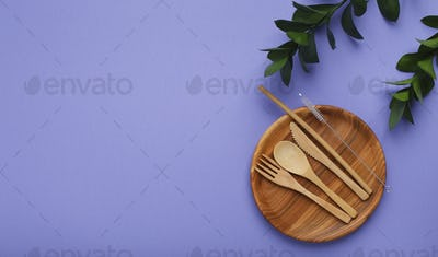 Wooden utensils. Plate and cutlery on violet background