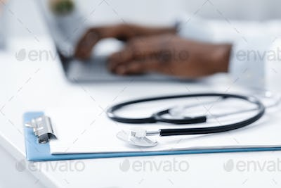 Stethoscope on medical chart over working with laptop doctor