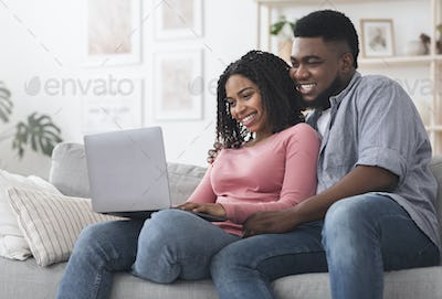 Cheerful Black Couple Using Laptop At Home, Ordering Food Delivery