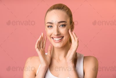 Cheerful Girl Touching Face Smiling To Camera, Pink Studio Background