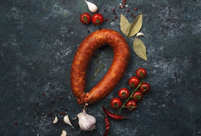 Smoked sausage on grey kitchen table background with aromatic herbs and spices