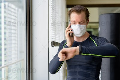 Young man with mask talking on the phone and checking smartwatch ready for exercising during covid