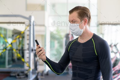 Profile view of young man with mask using phone at gym during corona virus covid-19