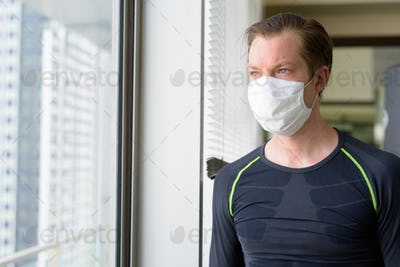 Young man with mask for protection from corona virus outbreak thinking of exercising during covid-19