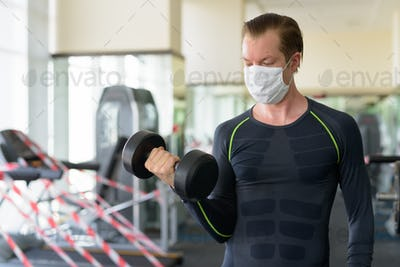 Young man with mask exercising with dumbbell at gym during corona virus covid-19