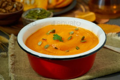 Closeup of pumpkin soup, autumn dish, healthy food, seeds and walnuts on background