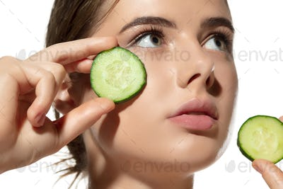 Freshness. Close up of beautiful young woman with cucumber's slices on her face on white