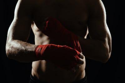 Close up boxer bandaging hands