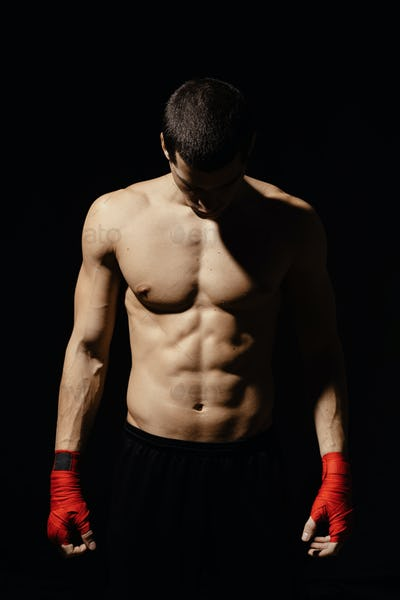 Athletic boxer getting ready before the fight over black background