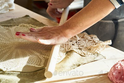 Woman making pattern on ceramic plate, hands close-up, focus on palms with clay