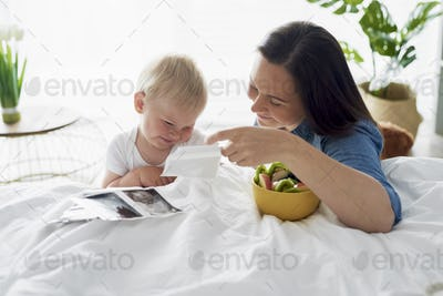Woman and her little son browsing pregnant photographies