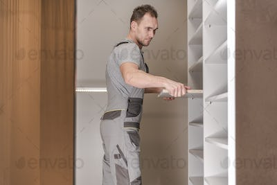 Constraction Male Assembling Cabinets In Closet.