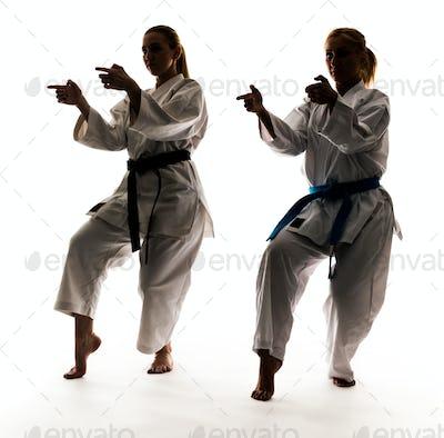 Two girls in kimono are training karate