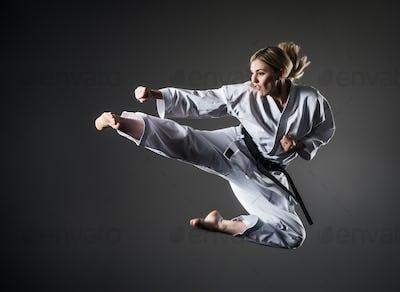 Composite image of karate girl jumping on dark background