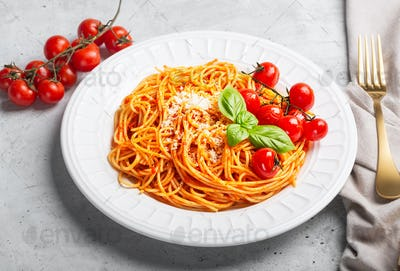 Spaghetti with tomato sauce and cherry tomatoes with basil on a white background, close up