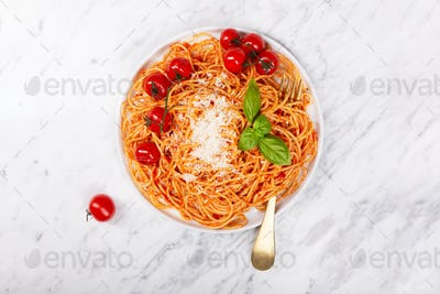 Spaghetti with tomato sauce and cherry tomatoes with basil on a white stone background