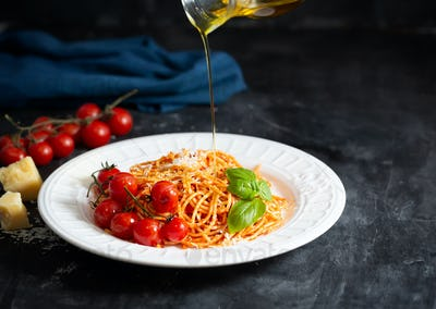 Spaghetti with tomato sauce and cherry tomatoes with basil on a dark background