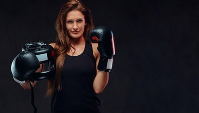 Beautiful brunette female boxer in sportswear. Isolated on dark textured background.