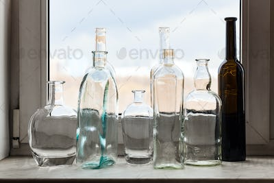 many empty bottles on windowsill and view of park