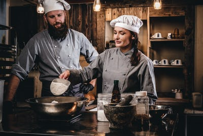 Chef teaching his assistant to bake the bread in a bakery.