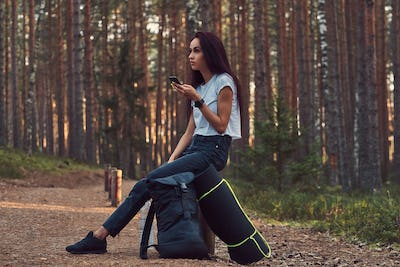 Tourist girl using a smartphone while sitting on a wooden post in a beautiful autumn forest.